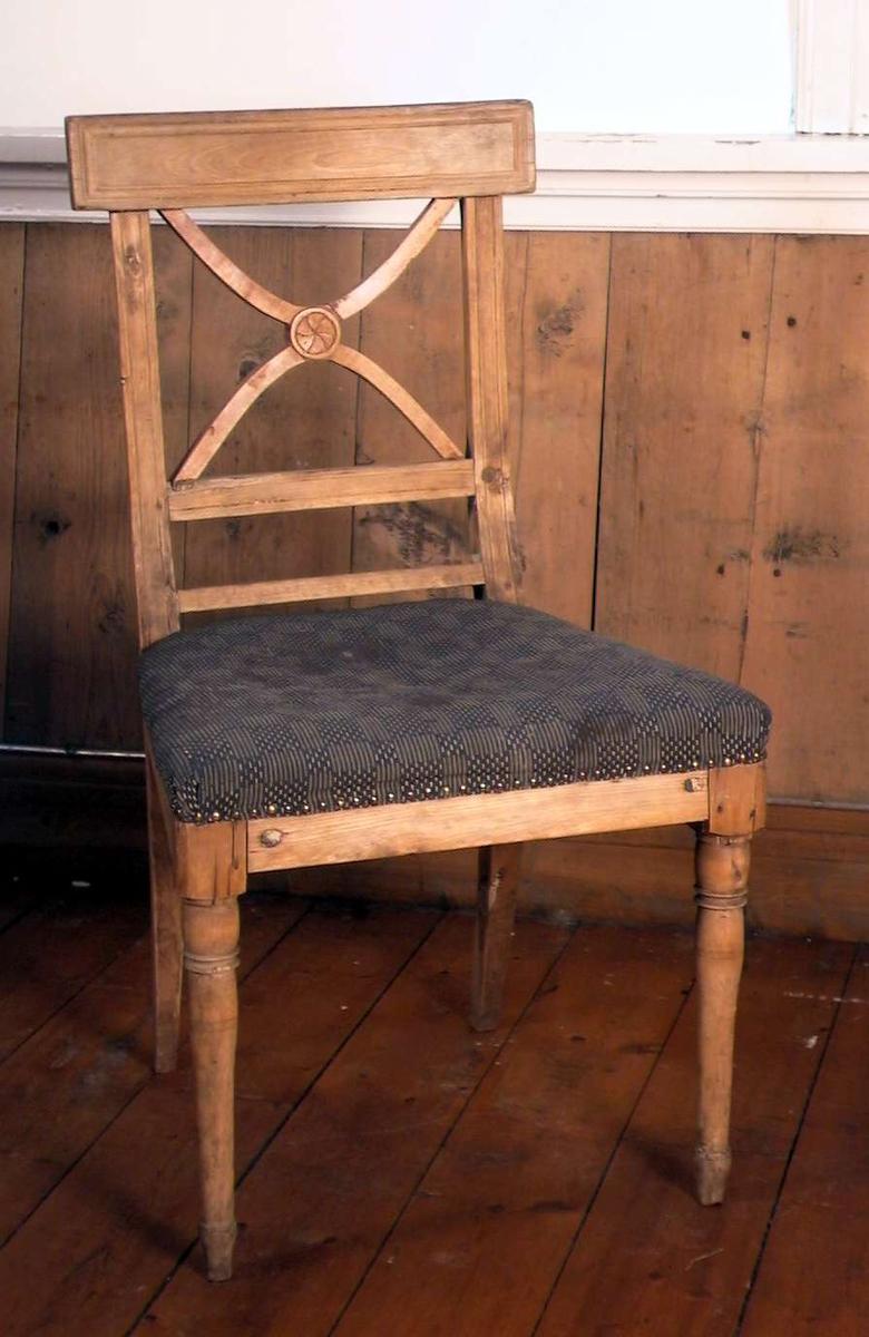 Trehvit spisestuestol med Andreaskors i ryggen og med stoppet sete. Stoffet i setet er blått og beige i et rutemønster. Trekket er flekket og slitt. Stolen er forsterket med jernbeslag.