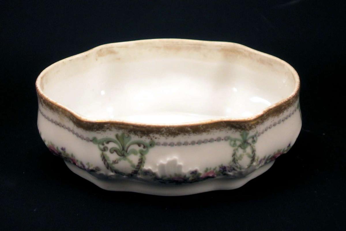 Skål i hvit porselen dekorert med girlander av blomster. Trykt dekor. Langs kanten er skålen forgylt. Skålen er oval med svungne linjer.