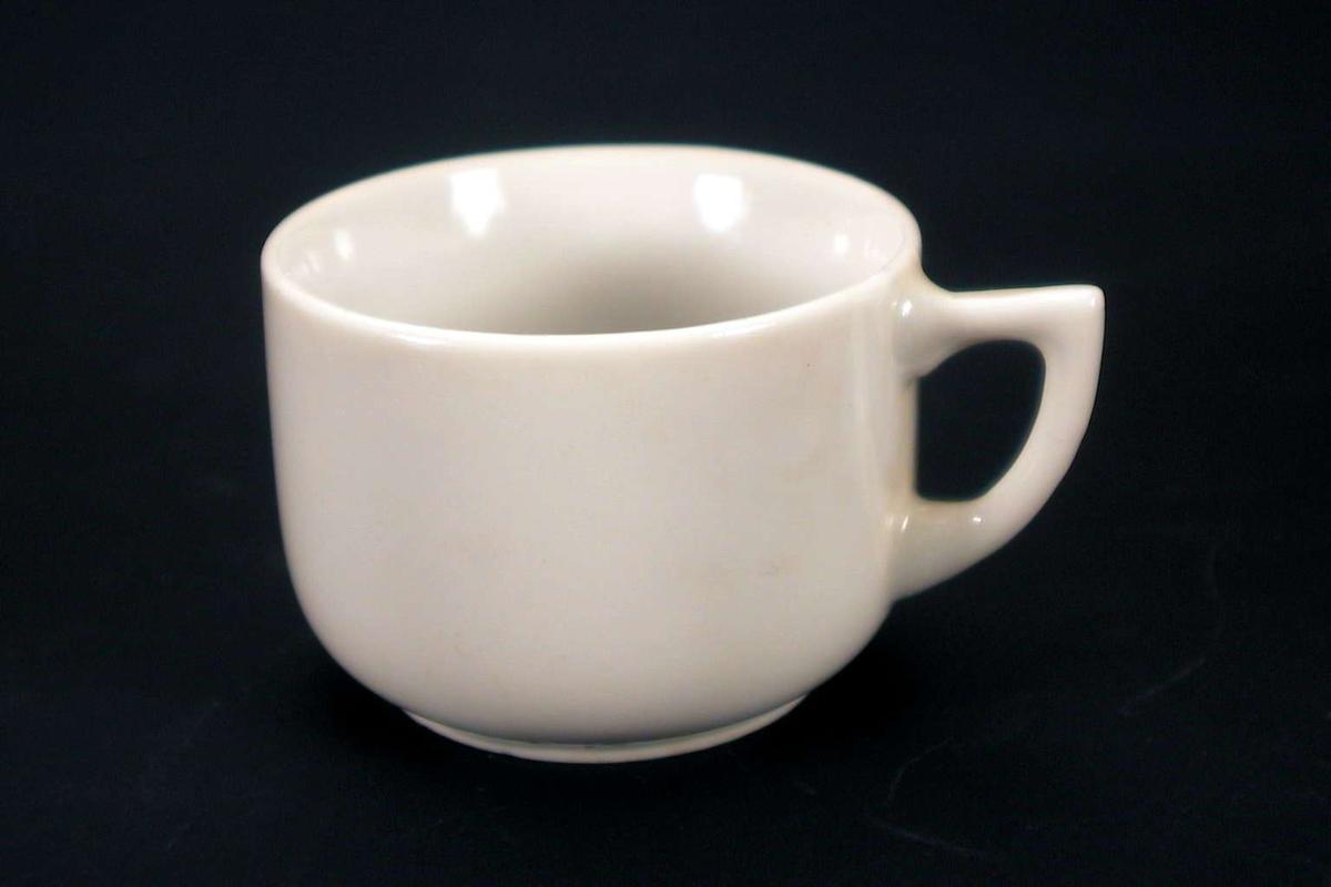 Liten, hvit kopp uten dekor. Den er stemplet 'Made in Japan', sammen med et merke med bokstavene OTO (eller OTC).
