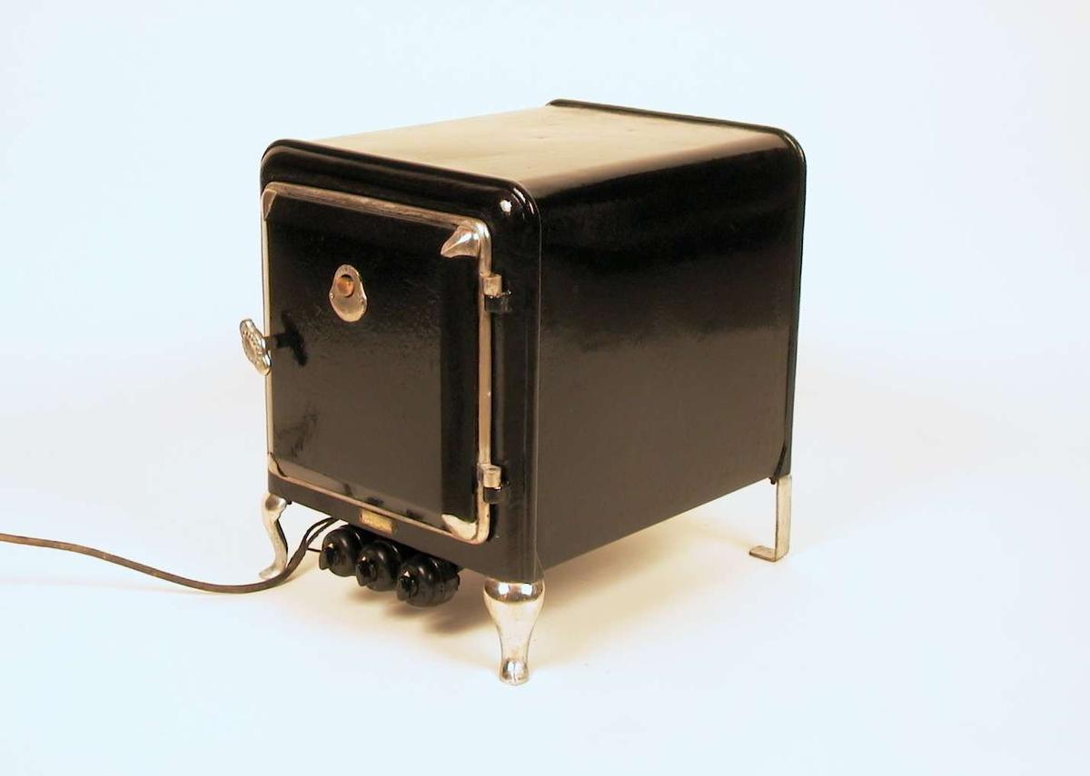Elektrisk stekeovn (uten kokeplater) i jern. Den er sort med blanke føtter, blankt håndtak og blanke lister rundt døren. Den har tre brytere med innstilling 'på 'og 'av'. Den har én løs stekeplate.