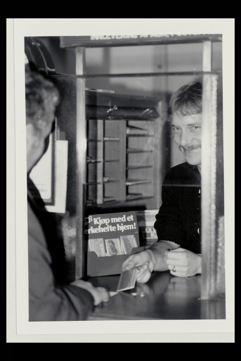 interiør, postkontor, salg av frimerkehefte til kunde, personal