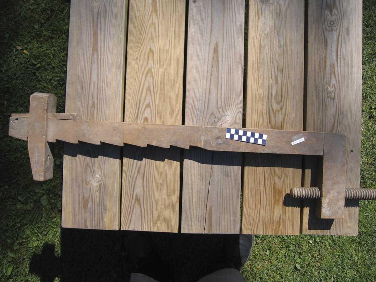 Limknekt i tre. En limknekt er i lang limtvinge med flyttbar overkjeve. Overkjeven er låst med sagtakket utskjæring og kile.