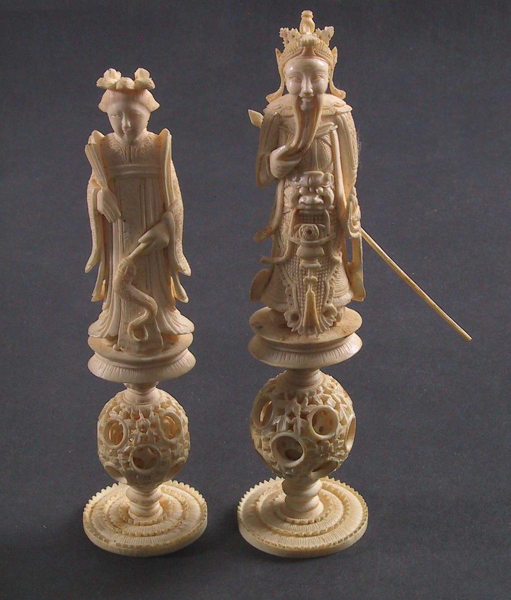 Sjakkbrett med brikker i elfenben og sinnoberfarget  elfenben Kina, 2.halvdel 1800 årene .  a) Sjakkbrett med tarok (eller likn) på innsiden.  lakkarbeid, sjakkbrett i sort og  gull. innvendig i sort, gull og rødt. På kanten: på hver side to paneler, begge med to menn. sort og gull. H. sammenlukket a 7.5.  Åpent 42,3 x 42,3 30 brikker, derav 14 hvite. Alle brikker er like, bortsett fra Kongen og Dronningen, som er forskjellig utformet. Av de flagg i toppen) og en av de små ryttere. Alle brikker står på føtter med en kule som er løs i en utskåret ytterkule (mys 15,4 og 15,5. H.ryttere 11. Tilstand: utmerket. En rytter løsnet fra kule og fot. Brettet har noen små skall i kanten i lakken. To hvite brikker mangler, en bonde og ett tårn.