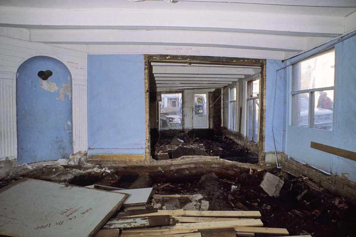 Tyholmen. Det gamle politikammer. 1. etg. Interiør, blåmalte vegger. Ovnsnisje., gulvet er brutt opp.