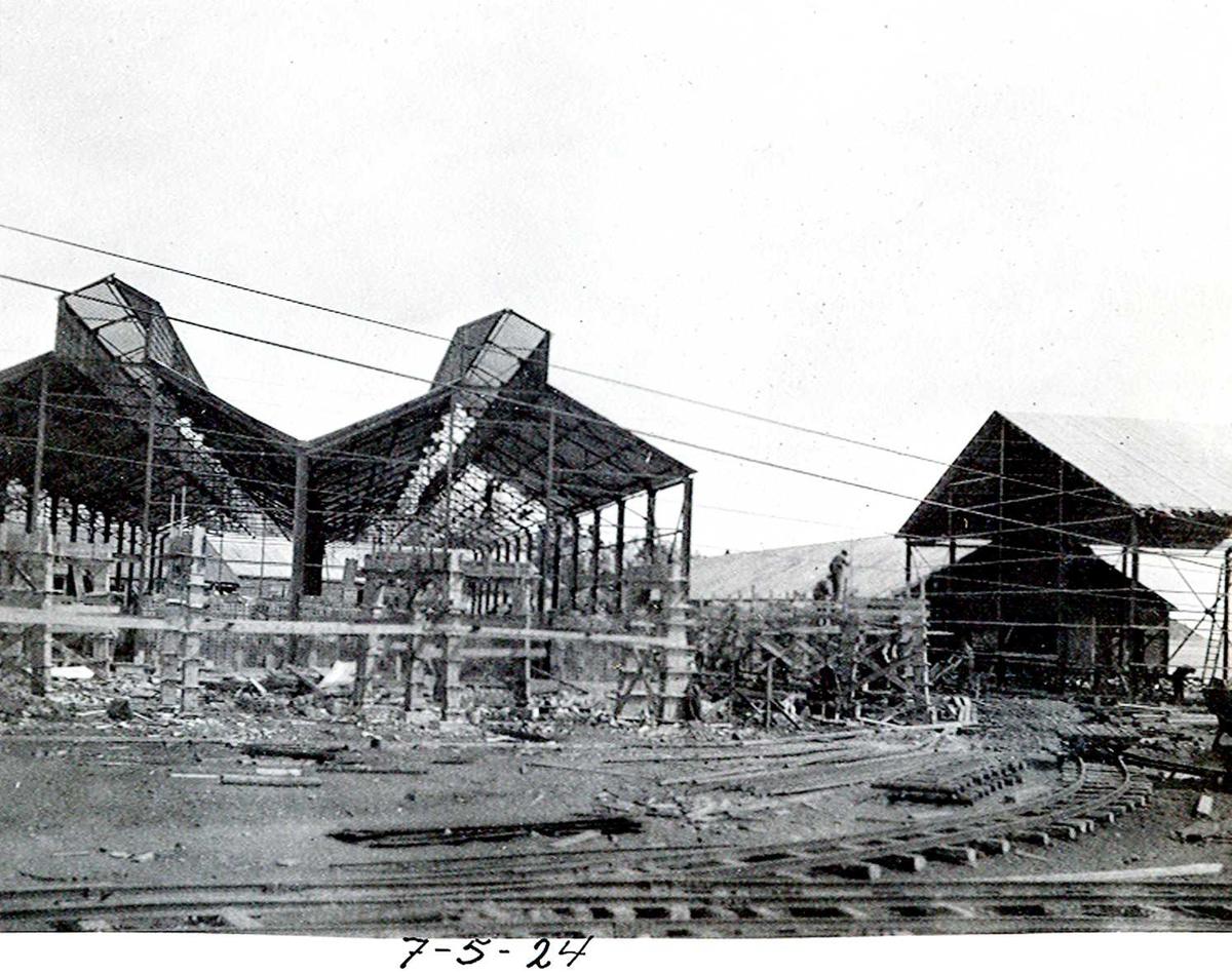 """""""07/05-1924"""" Nitriden. To bygninger for steking av elektrodekull under bygging. Skinnegang, """"høybanen"""", går inn i, og sør for, bygningen. Til høyre lagerbygning for ferdigprodukter. Skinnegang for internt transport i forgrunnen. Traller trukket av dieseldrevet lokomotiv."""