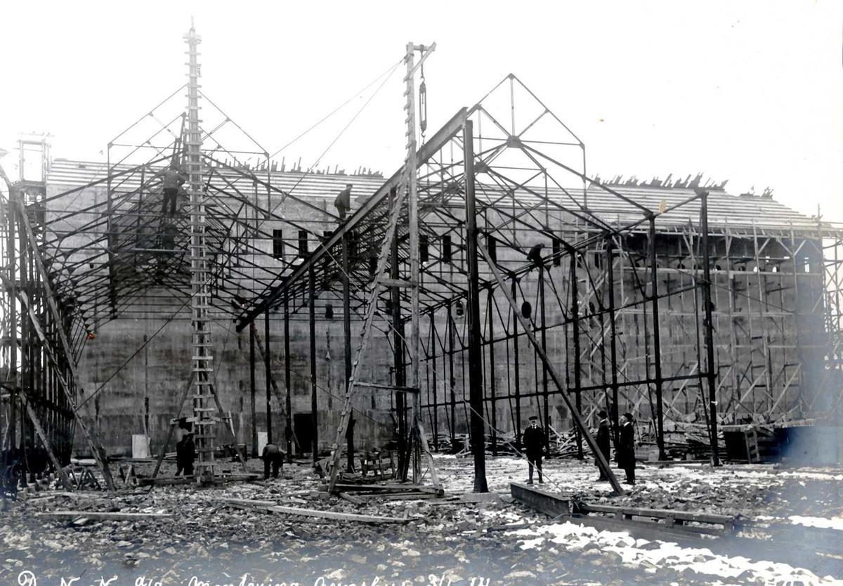 """""""03/01-1914"""" Nitriden. Reising av jernkonstruksjoner for Ovnshus I. Omformerstasjonen i bakgrunnen."""