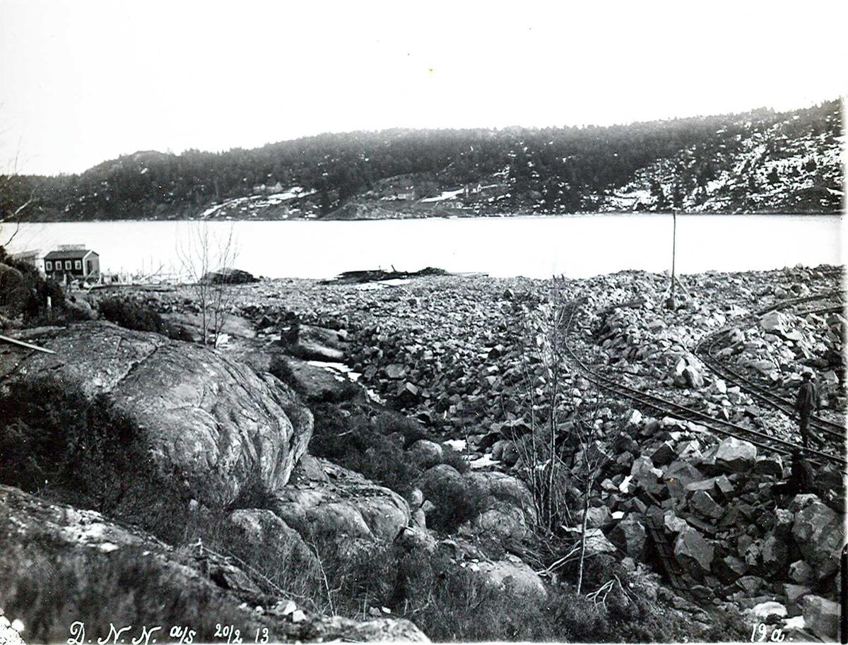 """""""20/02-1913"""" Nitriden. Utfylling og planering av fabrikktomten mot kai i Tromøysund. Tromøy i bakgrunnen."""