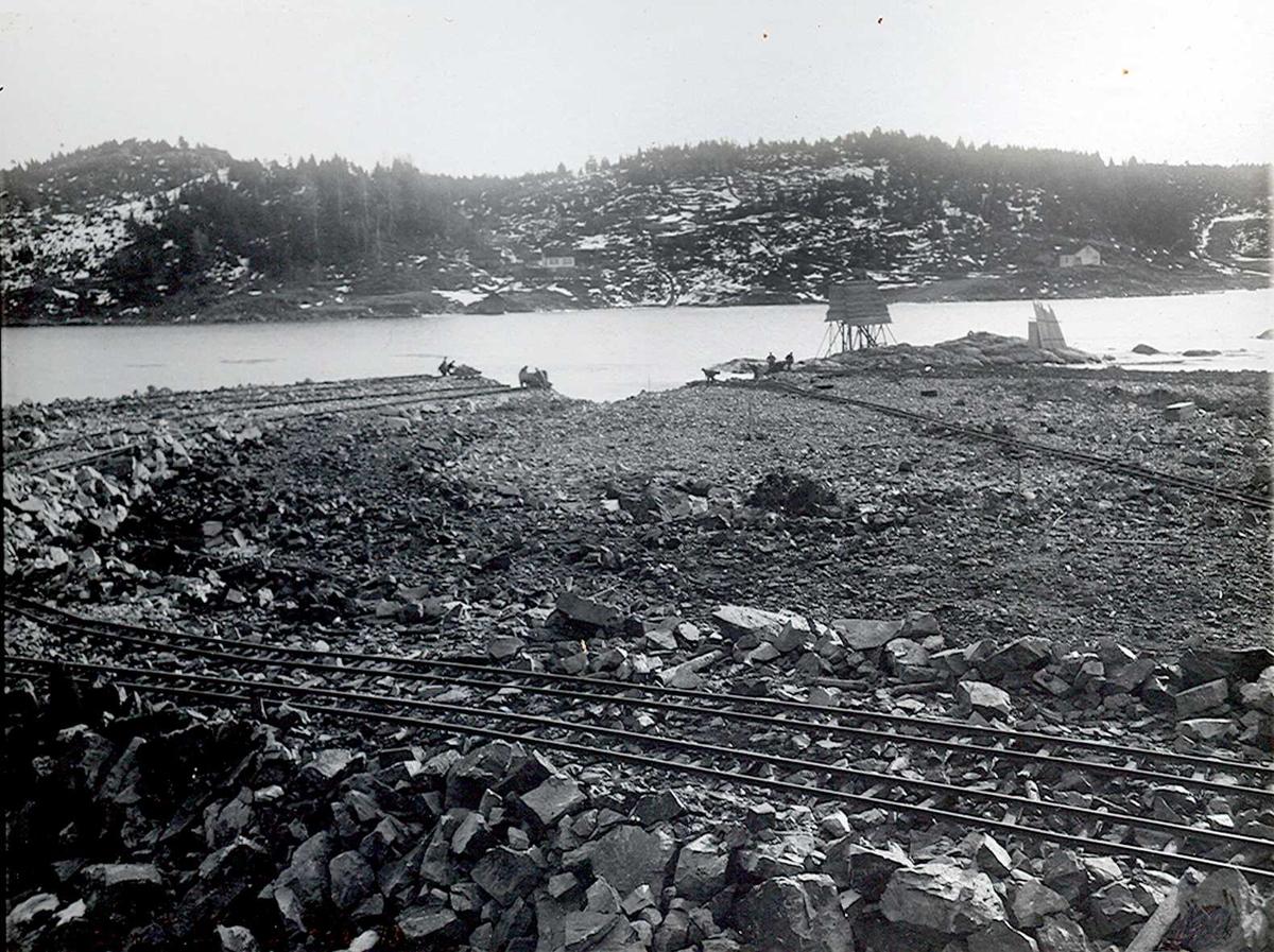 """""""1913"""" Nitriden. Utsprengning og planering av fabrikktomten mot Tromøysund. Tromøy i bakgrunnen. Kaianlegg skal bygges til venstre. Fyrlykt nr. 612 i Norsk Fyrliste bygget i 1894, flyttet til Friisøy, lenger vest, i 1929. (Skjermet)."""