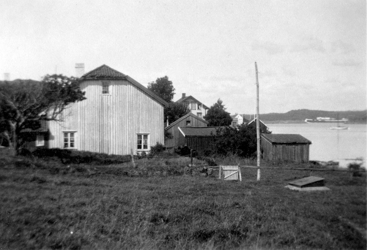Familien Wroldsens tidligere hus på østre Merdø, fotografert fra øst, fra sommerhuset Melleren. Flaggstang, to sjøboder med pulttak, brønn. Alle disse hus er revet. I bakgrunnen Merdøgaards sjøbod og Østerøen (Alma og Jens Mikkelsens hus). Gammel hage og port.