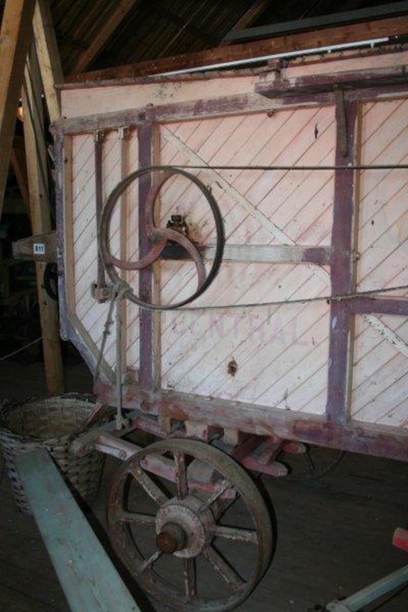 Stort verk på 4 hjul. Skråstilte bord i verkets sider.