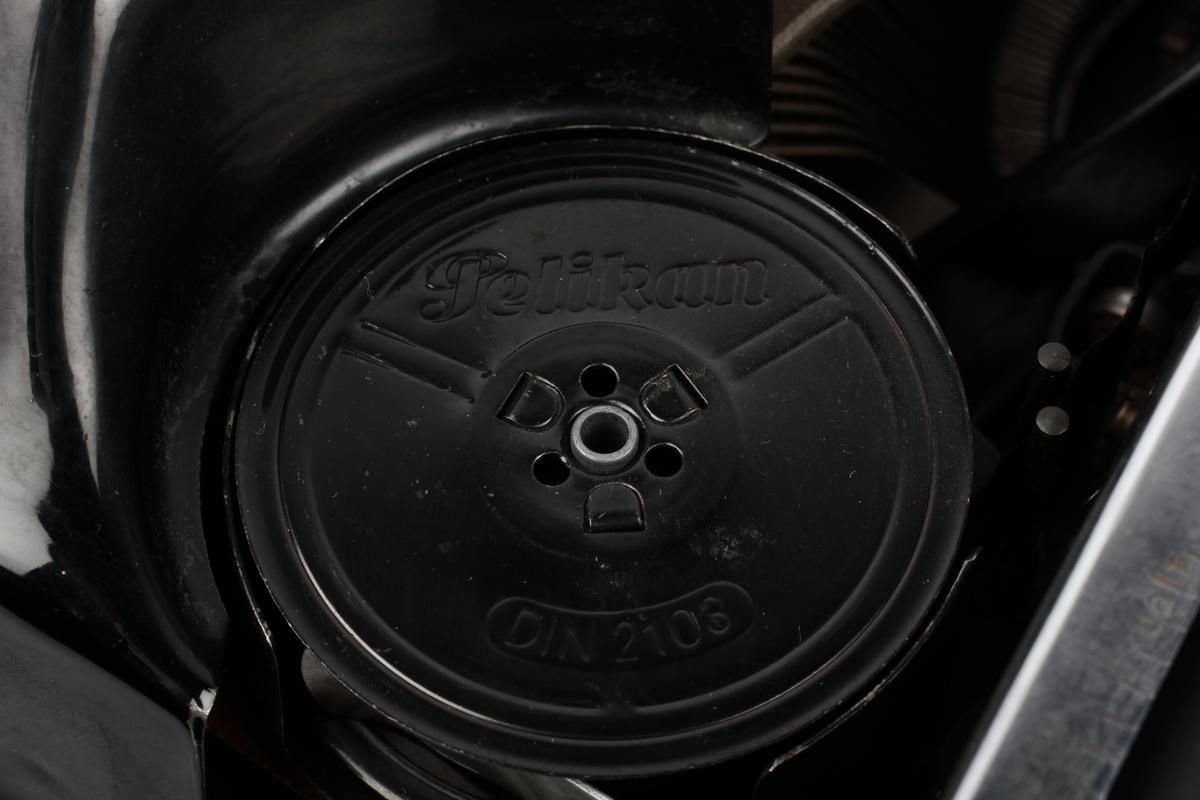 Manuell skrivemaskin med overtrekk av plast. Produsert for å være lydsvak.