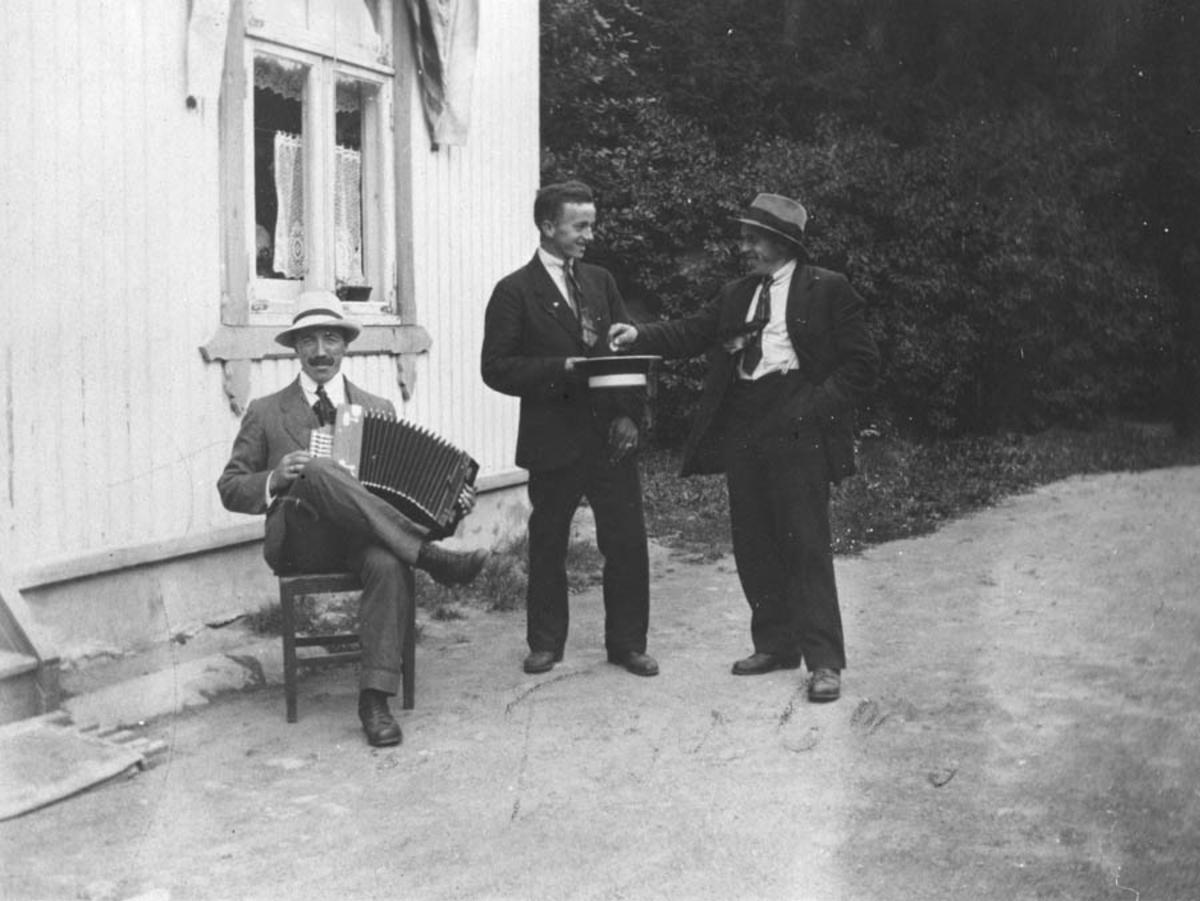 Gruppebilde. Tre menn, en mann spiller trekkspill. Henry Solberg samler penger i hatten fra Harald Høybraaten
