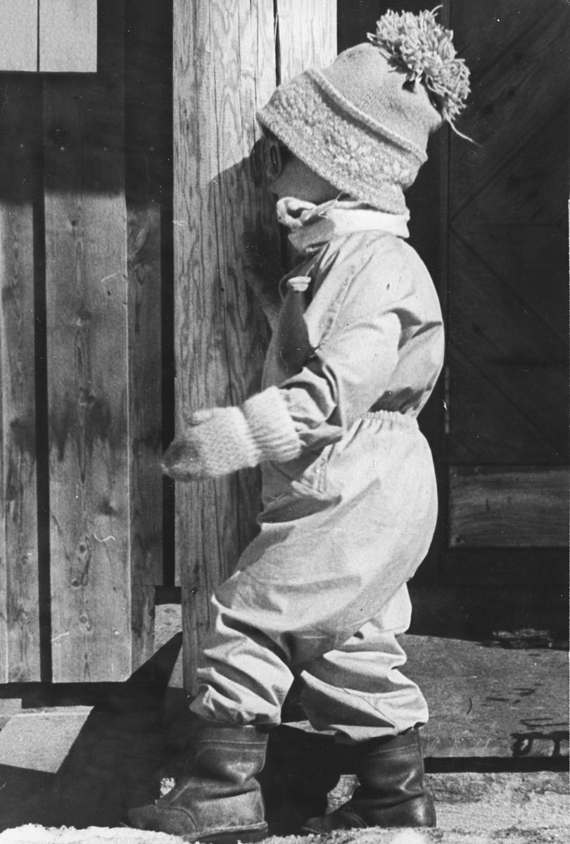 Liten gutt kikker igjennom sprekk i veggen