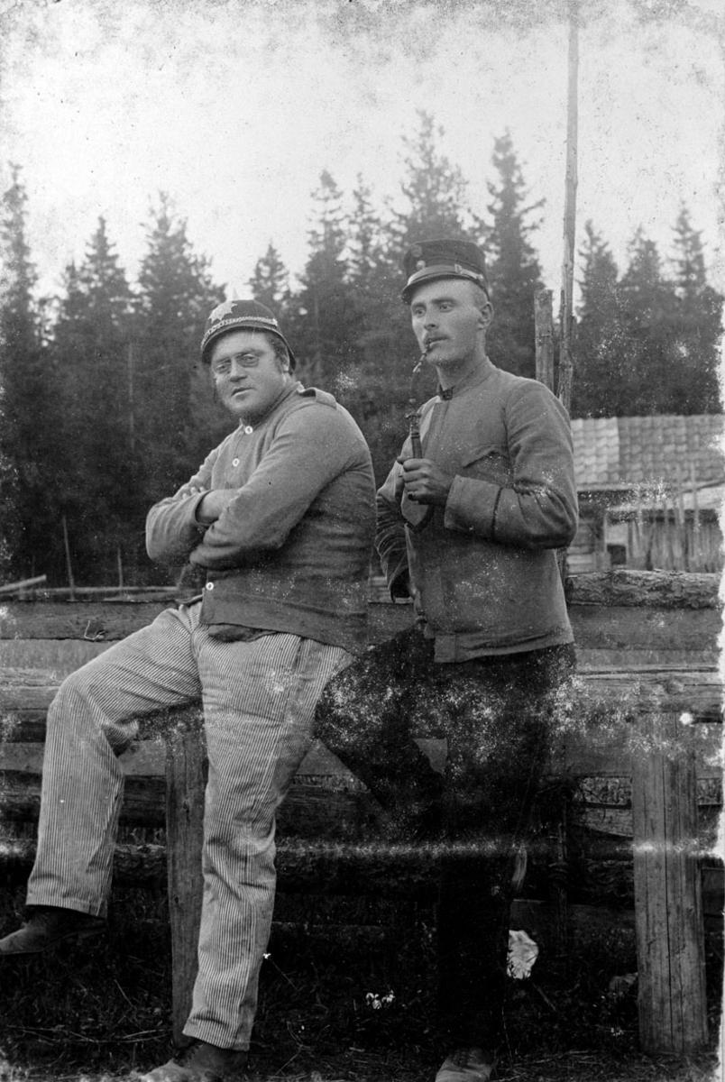 Gruppe på to mann i uniform, en med pipe i munnen.