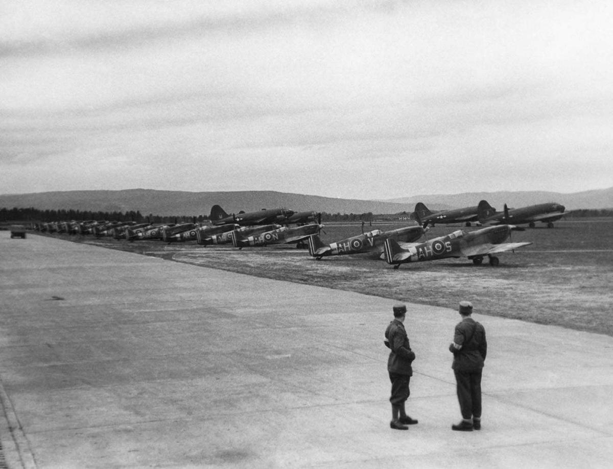 Gardemoen. Amerikanerne har flyutstilling. Juni / juli 1945. Flyene står oppstilt ved rulle banen, to menn i uniform står og ser på.