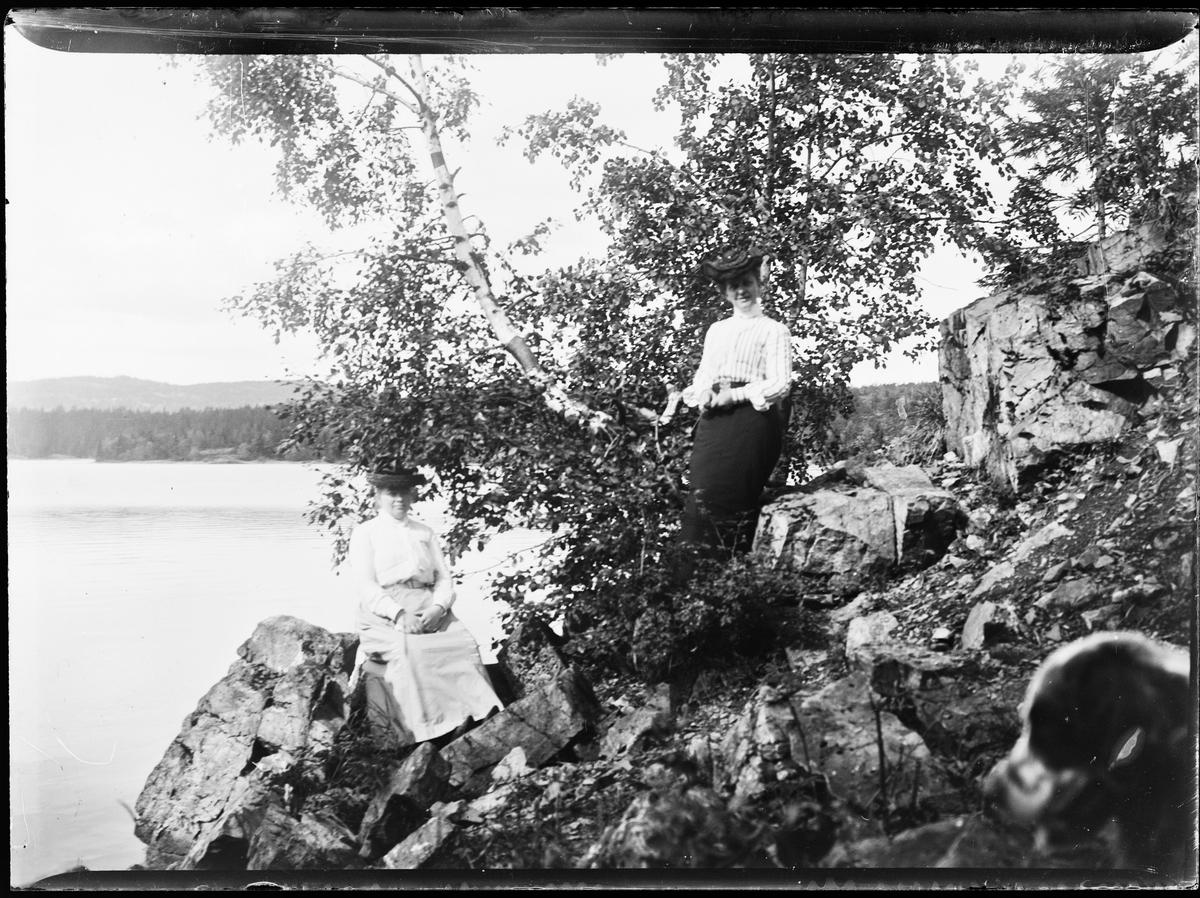 To kvinner ved vannet. Trær og steiner rundt dem. Et hundehode titter frem.