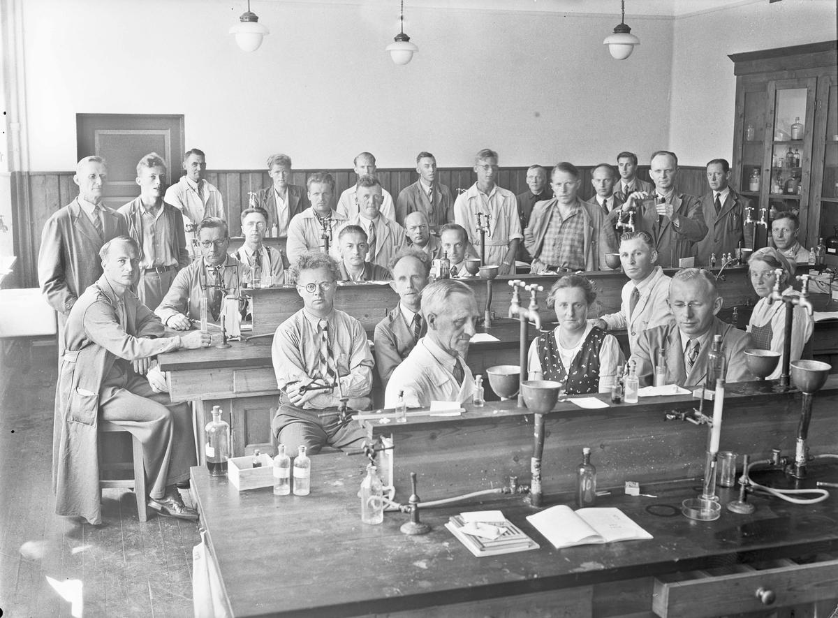 Gruppe voksne - sannsynligvis lærere - i kjemi-/fysikkrom.