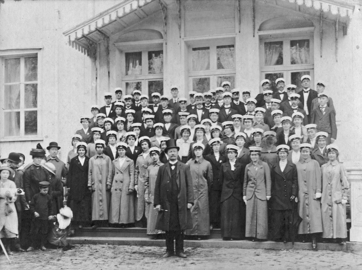 Eidsvoll manns- og damekor utenfor Eidsvoll Bad? Ca. 1915-20. 100-års jubileum for Grunnloven? Hans Nilsen Johnsrud dirigent.
