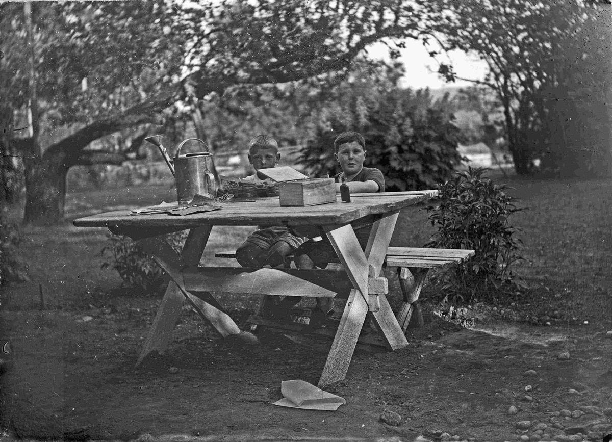 To barn sittende ved et bord utendørs