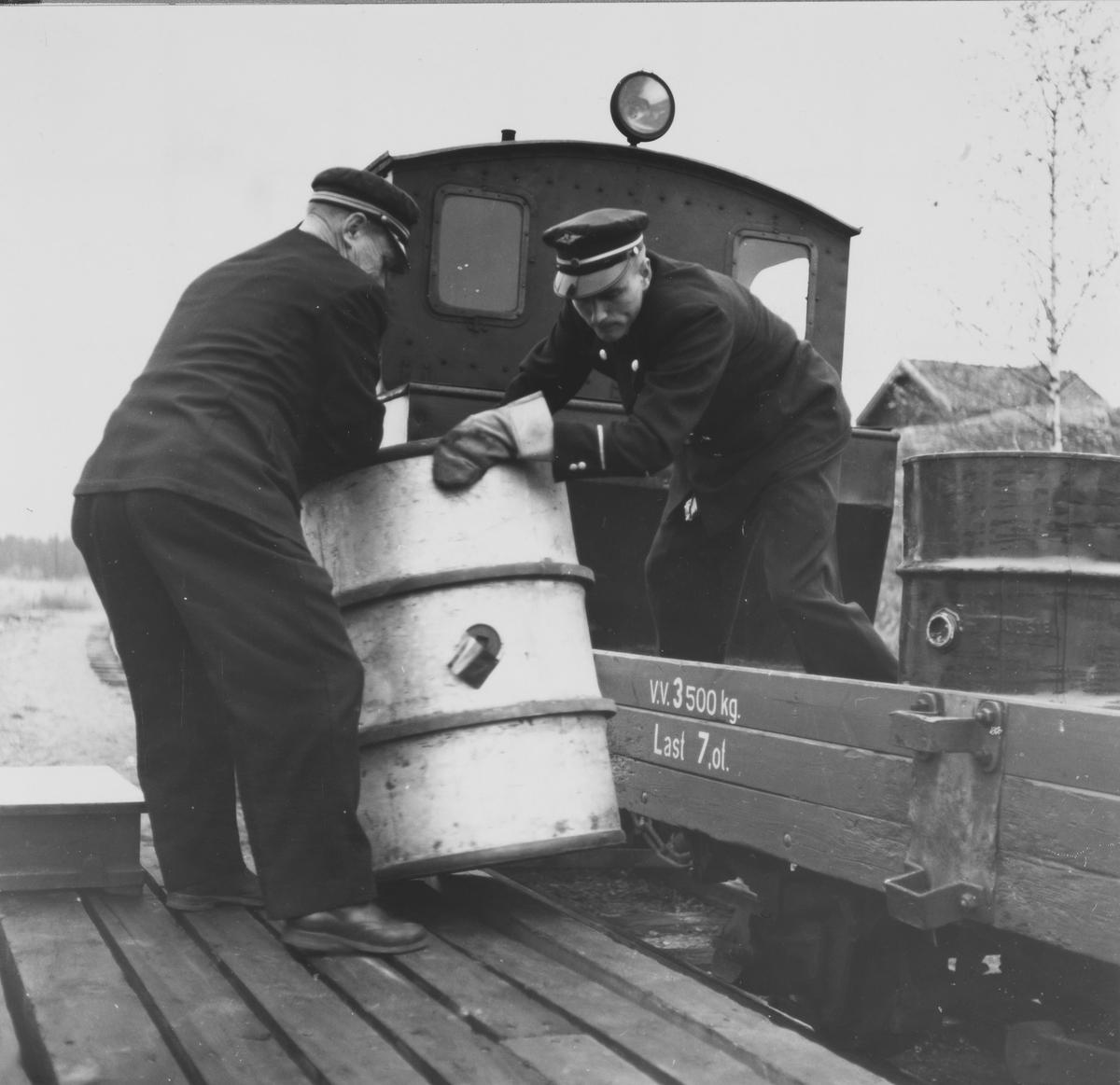 Overkonduktør Rolf Ødegård og konduktør Sigmund Furustad losser et oljefat fra en N-vogn. Tog retning Skulerud