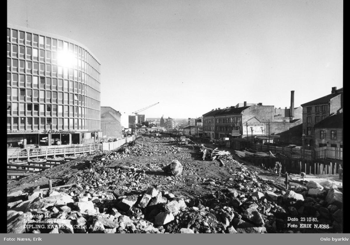 Byggingen av Jernbanetorget stasjon, Traktorhuset i Nygata 12 til venstre, Vaterland saneres. Bilde datert 23. oktober 1963.