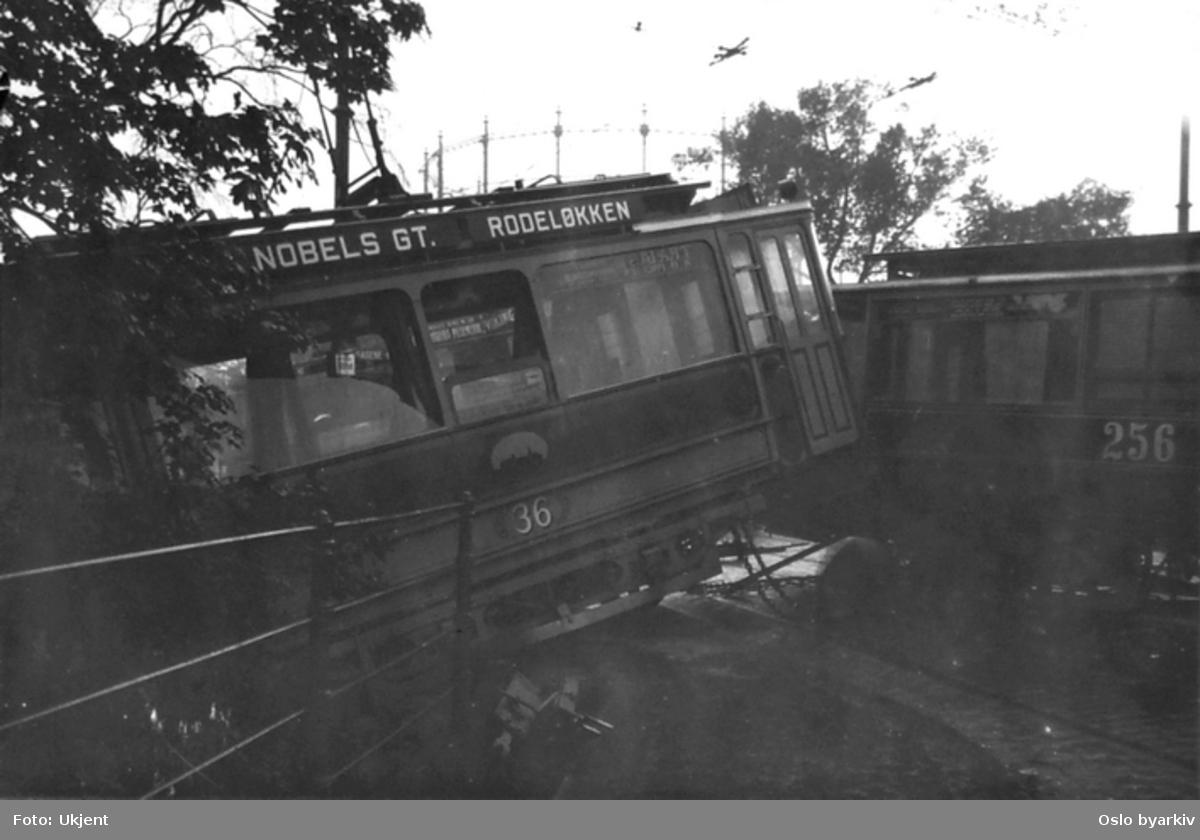 Bildet er tatt 16. juni 1916 etter at et vogntog på linje 9 fra Rodeløkka hadde fått problemer med bremsene og kolliderte med et vogtog som skulle oppover Thv. Meyers gate på Nybrua. Det løpske toget sporet av og holdt på å kjøre utfor Nybrua og ned i Akerelva, men ble stoppet av et bjørketre.Fotograf er trolig Aftenposten. Trikk type U nr. 36 og tilhenger type kommunal ombygd nr. 256.