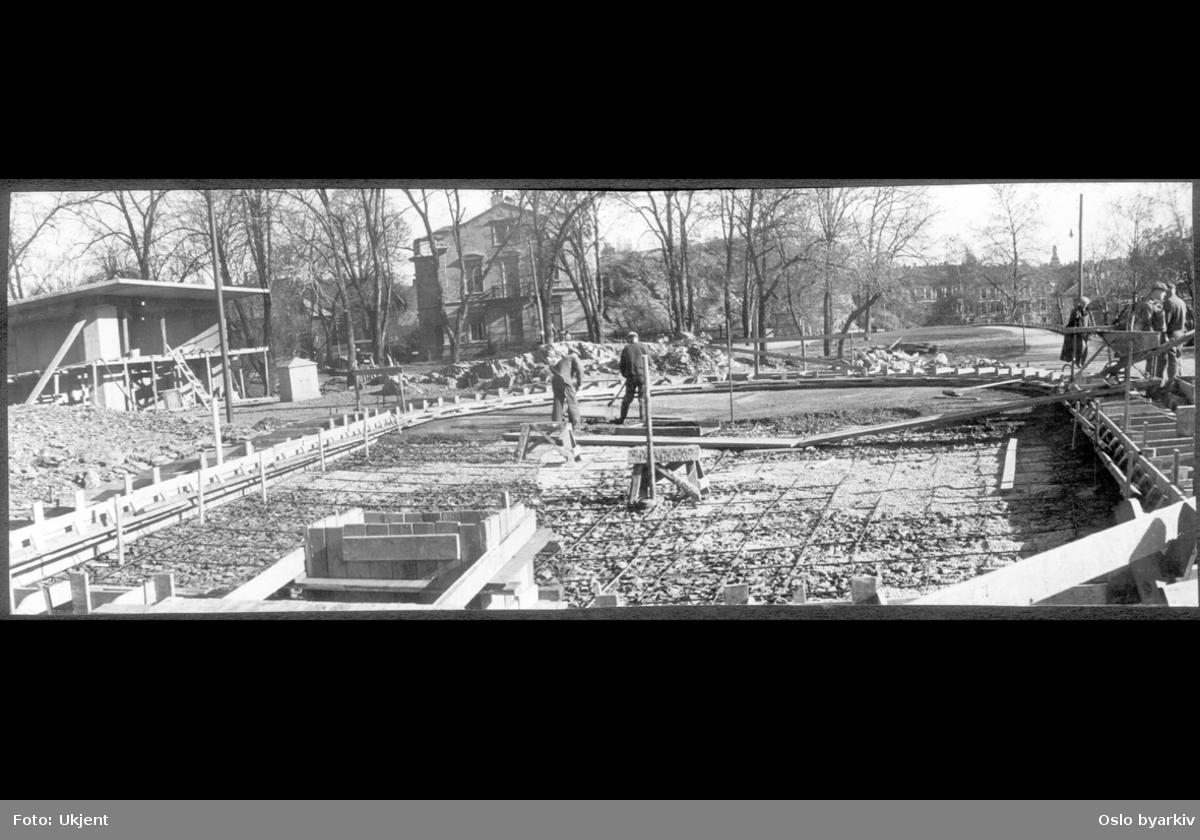 Opparbeidelse av vassebassenget / plaskedammen på toppen av parken. Arbeidere med sementlegging på armeringsjern over stein- og grusunderlag. Leskur i funkis-stil til venstre.
