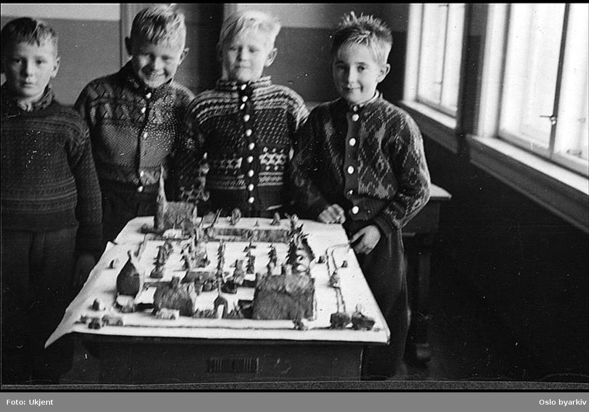 """Stolte elever viser fram modell i leire fra lokalmiljøet.(Formingsundervisning). Albumtittel: """"Sofienberg skole femti år - første september 1933."""""""