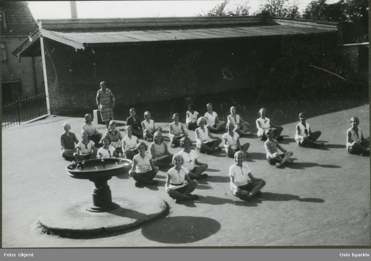 """Pikeklasse i skolegården har gymnastikktime. (linjegymnastikk) Albumtittel: """"Sofienberg skole femti år - første september 1933."""""""