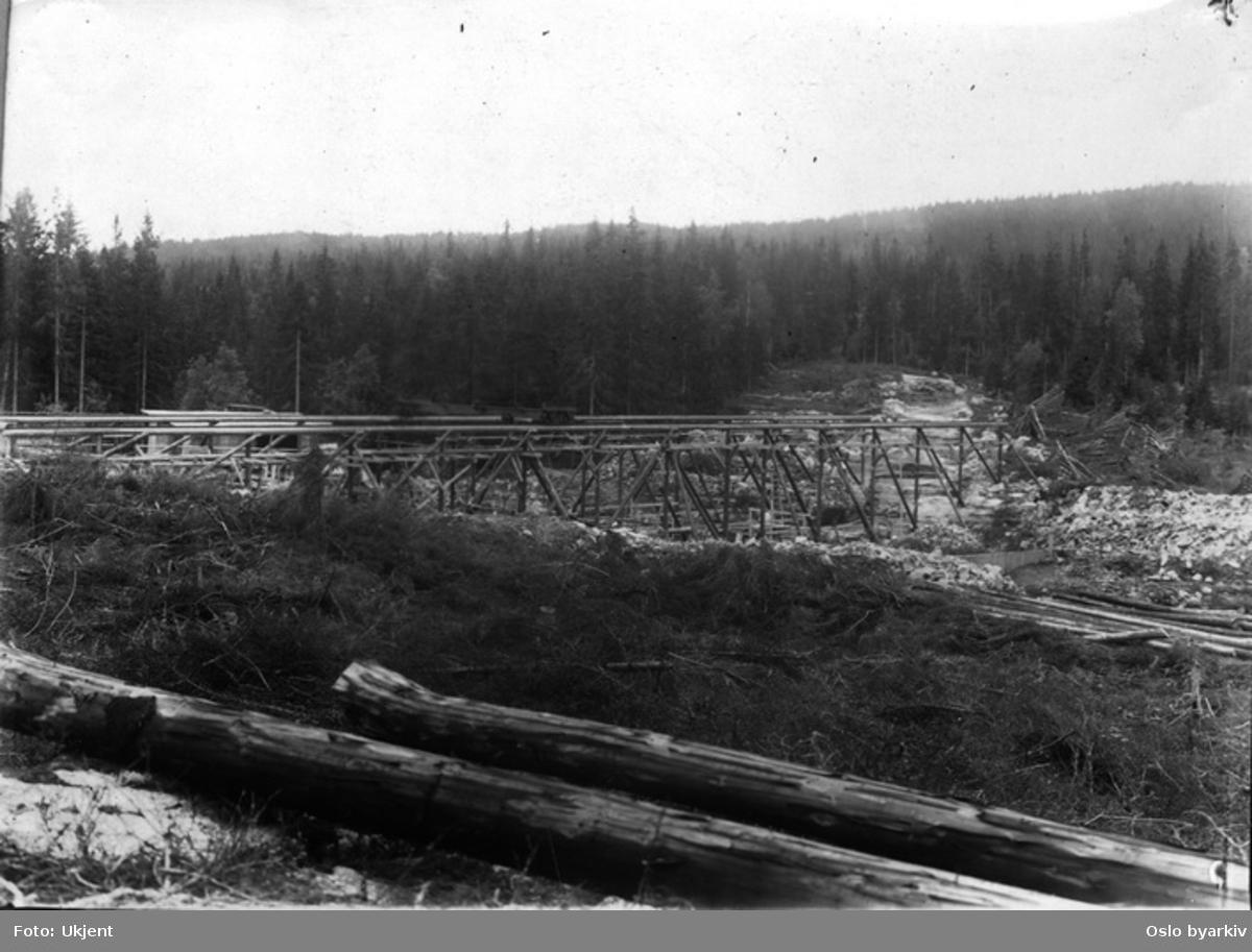 Byggingen av den nye Øyungsdammen (ferdig 1916). Reisverk i tre. Tømmerstokker.