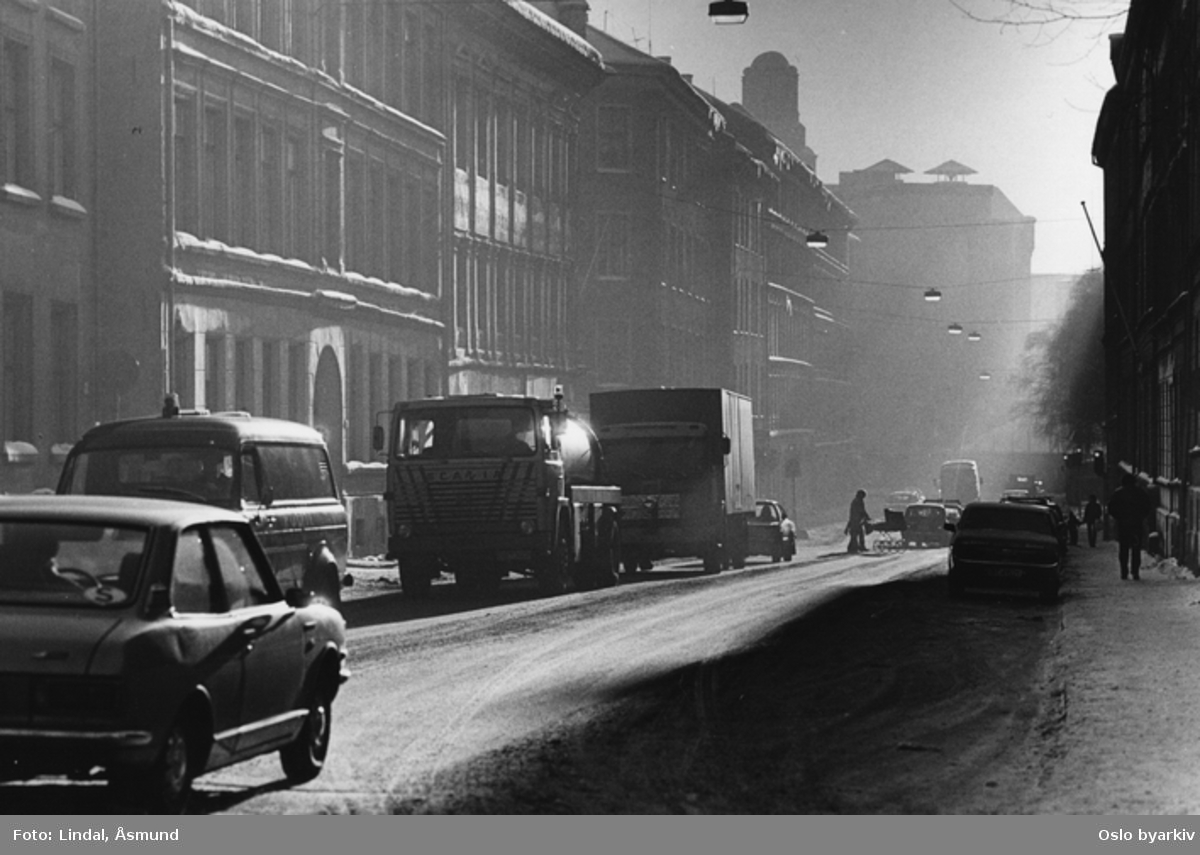 Gate med stor trafikk med lastebiler og biler. Trafikkmiljø. Fotgjenger på vei over gata med barnevogn. Fotografiet er fra prosjektet og boka ''Oslo-bilder. En fotografisk dokumentasjon av bo og leveforhold i 1981 - 82''. Kontakt Samfoto ved ev. bestilling av kopier.