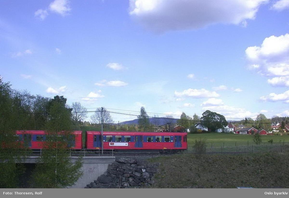 Oslo Sporveier. Kolsåsbanen. T-banevogn, serie T5, i tog på linje 4 på vei over brua over Gjønnesjordet. Gjønnes gård i bakgrunnen.