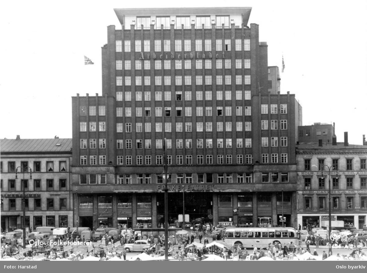 Folketeaterbygningen, Folketeatret, Arbeiderbladets kontorbygg, fasaden mot Youngstorget (Nytorvet inntil 1951). Torgsalg, torgboder, buss, biler. Postkort 1654? A 2.