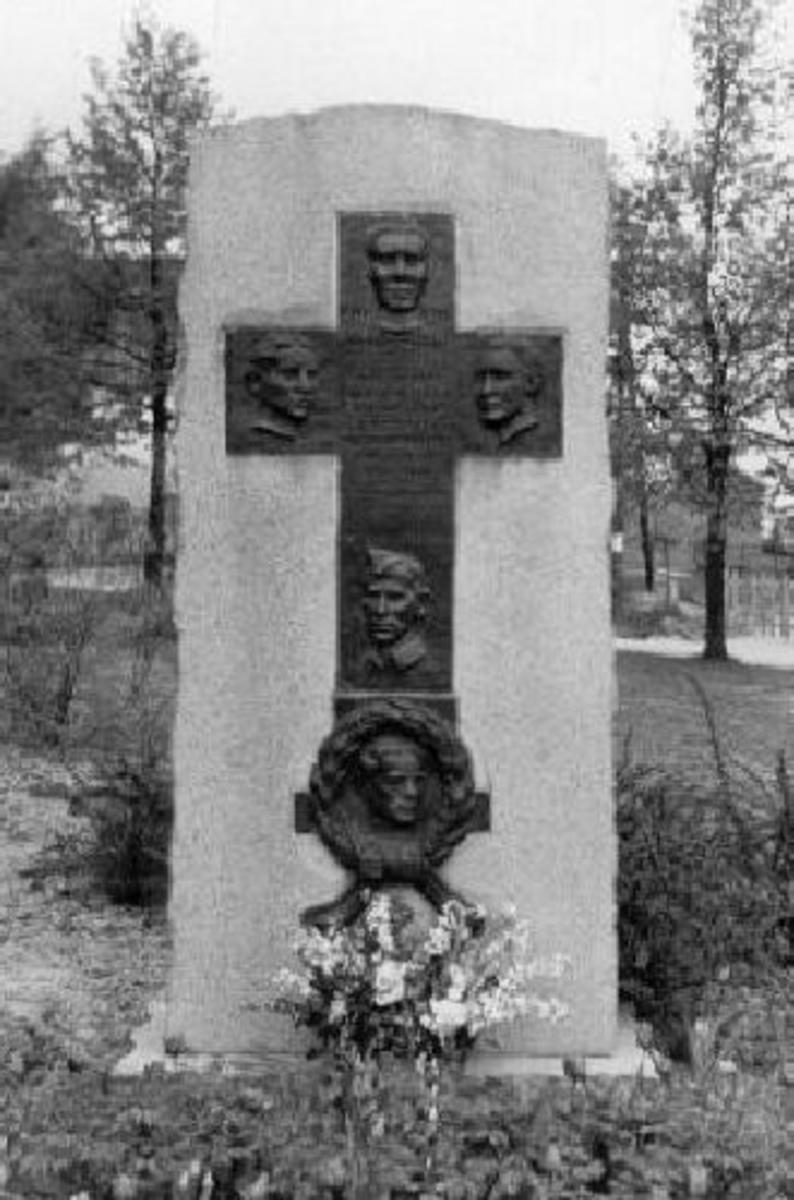 Krigsminnesmerke. Bauta med relieff. Bronse-relieff på granitt-støtte. Høyde 240 cm, bredde 110 cm, dybde 42 cm.