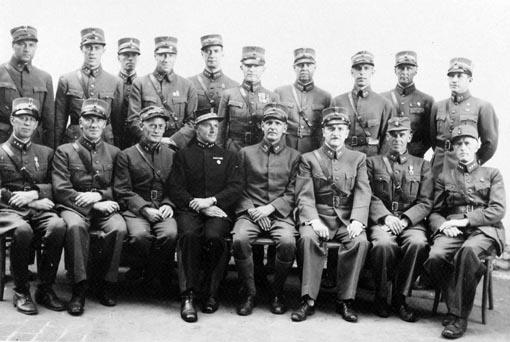 Gruppe 18: norske offiserer i militæruniform, Schildberg fangeleir i Polen under 2. verdenskrig, krigsfanger, nr. 2 fra venstre: Kaptein Knut Stai (1898-1986), nr 4 fv: kaptein Teodor Koller fra Ringsaker. (Fjeld) Bakre rekke nr. 6 f.v. Kaptein Sigvard Tallaksen(arrestert 16.08.1943, og deretter sendt til Shildberg fangeleir i Polen. Senere overført til Luckenwalde hvor han satt til freden.