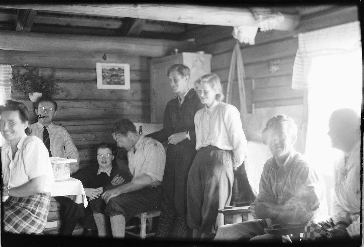 Interiør, hytte. Gruppe kvinner og menn. Fra venstre Ingeborg Haugen, Lars R. Haugen, ukjent, ukjent, Arne Vea, Agnes Vea, Mikael Eriksen, ukjent