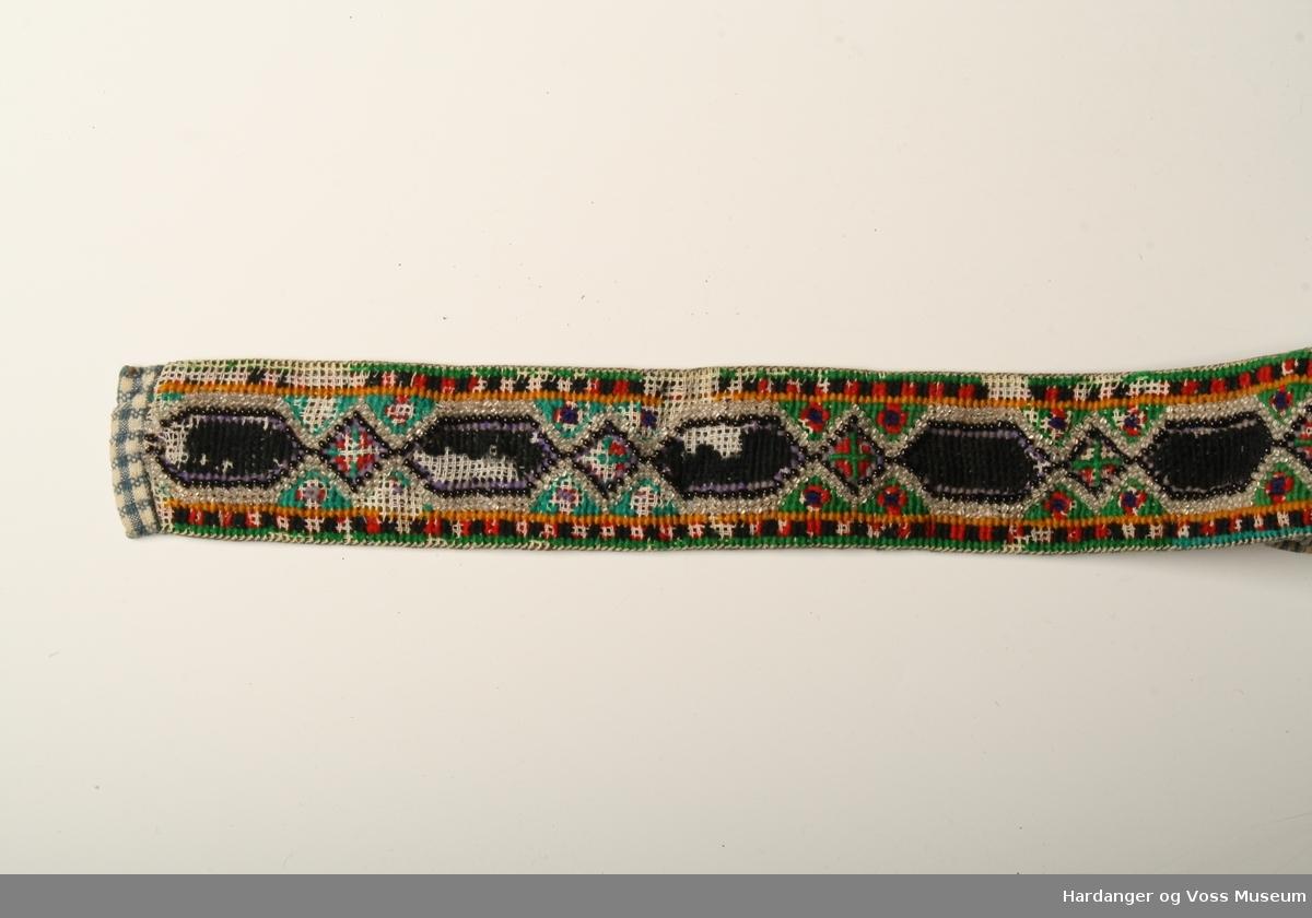 4881a566 Mønsteret er sydd med ulltråd i kross-sting og perler. Metallspenne på den  eine. Photo: Hardanger og Voss Museum