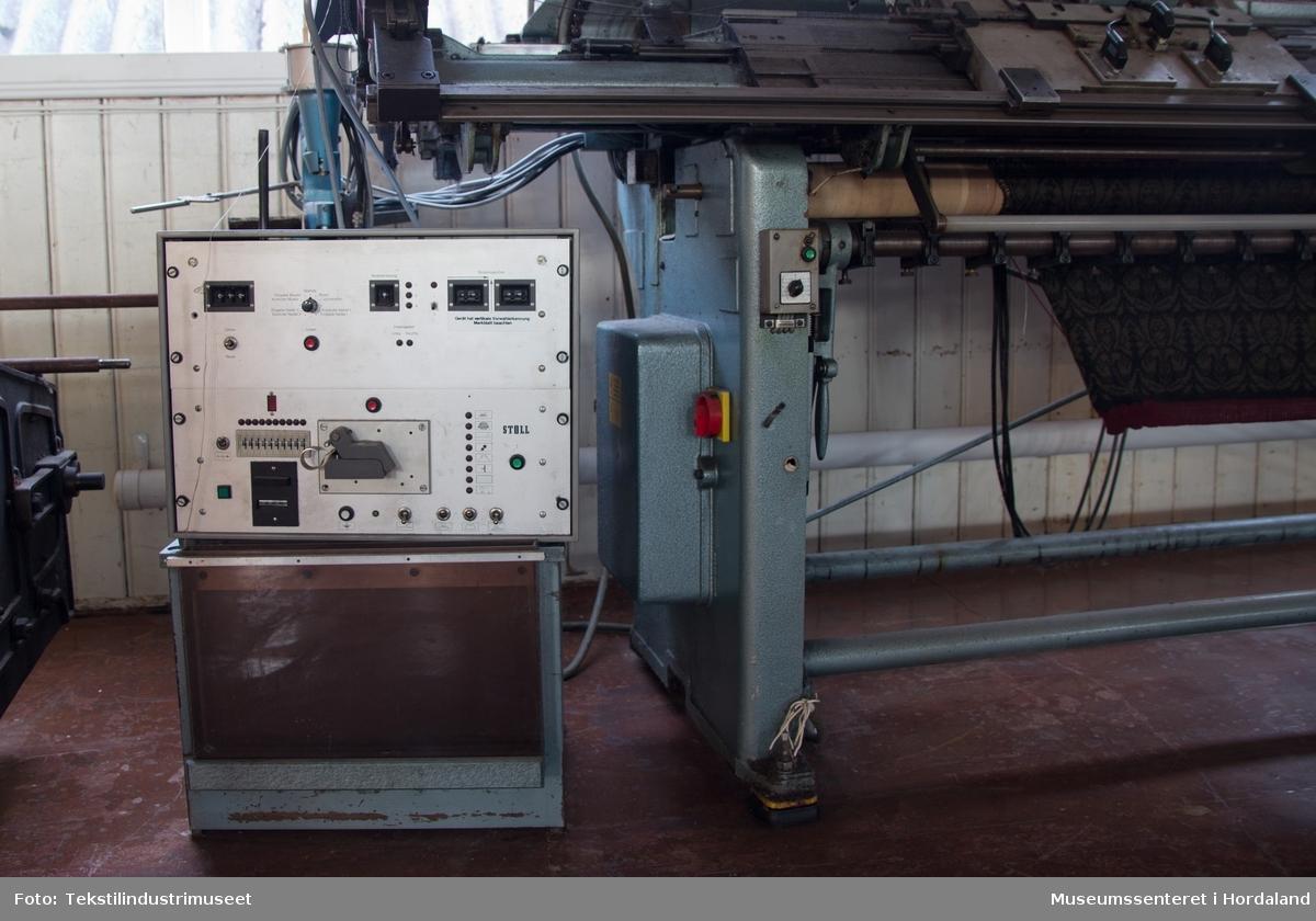 Elektrisk styrt flatstrikkemaskin med eit raudt brett til garnkoner over sjølve maskina, og trådbaner øvst. Det at den er elektrisk styrt, gjer mellom anna til at maskina vil stoppe automatisk om t.d. ein tråd ryk. Maskina har ein boks på høgre sida som brukast til å programmere mønsteret, ved å mate ein tynn 'hullfilm' inn i maskina. Maskina strikkar ikkje metervare, men ferdig bol og armar til gensarar.
