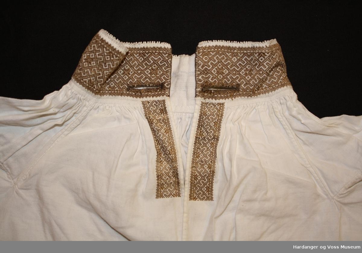 Skjorta er sydd i primærsnitt med innsydde kilar ved hals og under erma. Skjorta er rynka kring halslinning. Knapphol på kvar side av halslinning. Skjorta har opning eit stykke ned framme, med svartsaum 7 cm ned frå halslinning. Skjorta er påskøytt nede.