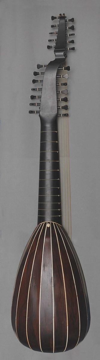 Pæreformet kropp. 5x2 basstrenger, 6x2 + 2x1 tarmstrenger over gripebrett med 11 tverrbånd, også av tarm, Bunn består av 9 spon av palisander, fuget sammen med 3-5 mm tykke striper av elfenbein. Konstruksjonen forsterket på nedre kanten med en kappe av palisander. Endeknapp på nedre kant samt på undersiden ved halsfugen (for rem til instrumentet) Lokk i nåletre, muligens furu(?) med innlagt kantlinje av elfenbein. Meget tette årringer i strengeretningen. Bronsert rosett i fire dybde-plan av hardt papir, limt på struktur av tynt utskåret brunmalt tre (ukjent materiale). Rundt rosetthull er 2x3 linjer (elfenbein, ibenholt, elfenbein) samt små rektangler av elfenbein og uidentifisert tre (mørkt) mellom gruppene. Stol, egentlig strengefeste, av ibenholt eller beiset frukttre med innlegg av elfenbein. Strengene festet i stolen og knuten danner ene endepunkt i den klingende strengen. Hals med avrundet underside, av beiset tre (frukttre?), gripebrett av tynn ibenholt med en ramme av elfenbein (ca15mm). Innlagde plater av ibenholt og elfenbein ved halsfuge. Oversadel ved gripebrett av elfenbein; oversadel for basstrenger av beiset tre (integrert i øvre skruekasse). Beiset fuge mellom hals og skruekasser (eg. mellom 1. bånd og oversadel), også av frukttre? To skruekasser som er i en stykke. 14 + 10 stemmeskruer av ibenholt med dekorringer og små knopper i distale enden av elfenbein. [MK/VdB 14.05.2009]