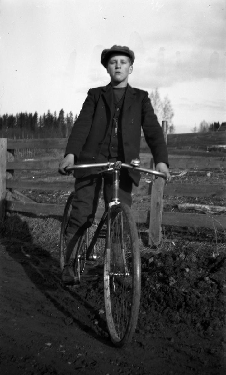 Ukjent gutt på sykkel langs en vei med gjerde.