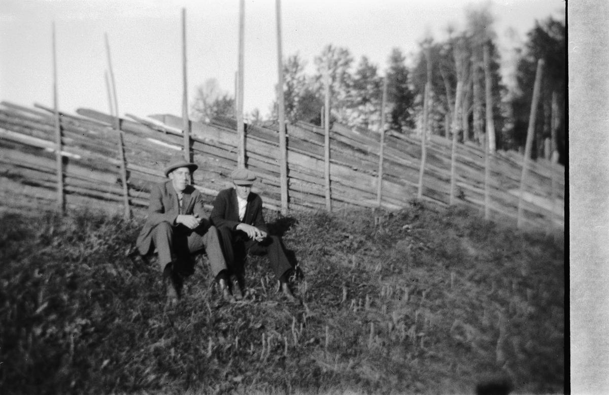 To menn sitter på gresset ved en skigard.