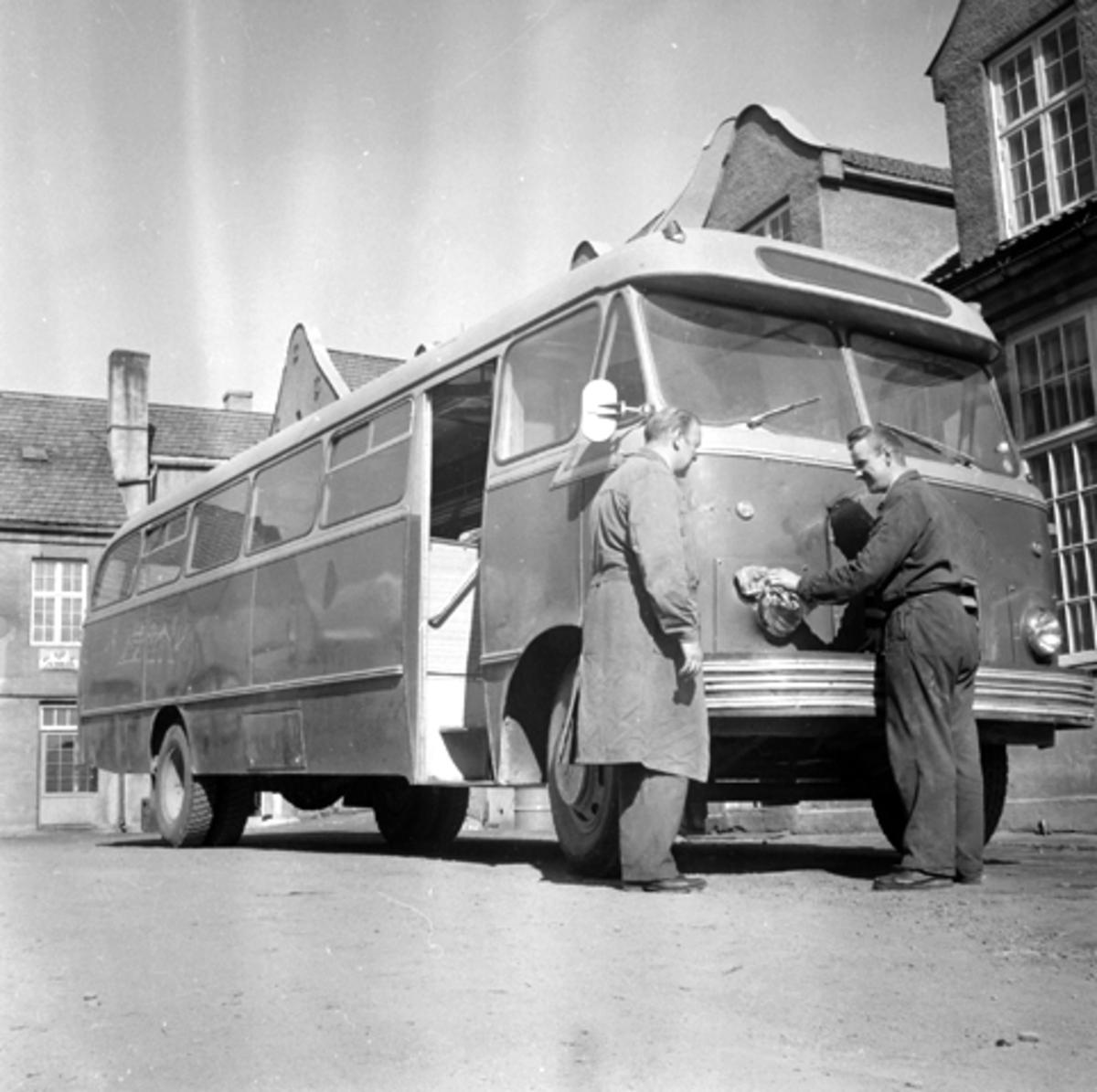 Buss foran Oustad. To menn foran en buss.