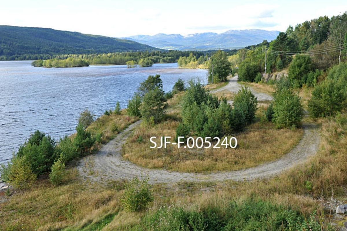 Den tidligere utislagsplassen for tømmer ved Aslaksborg i Sauherad i Telemark. Fotografiet er tatt fra en bergskrent i sørenden av plassen.  I samband med Sundsbarmutbygginga ble det i 1970 planert en stor, oval plass på Aslaksborg, hvor lastebiler kunne levere tømmerlass for buntfløting over Norsjø og ned til Skien.  Målet var at det fortsatt skulle være mulig å fløte tømmer fra kraftverkets nedslagsfelt på i den delen av vassdraget som ikke var berørt av utbygginga.  Kraftutbyggerne bekostet både plassen og adkomstvegen.  Ved Aslaksborg ble det på det meste levert 60-70 lass tømmer i døgnet.  Også mye av transporten ble betalt av kraftselskapet, som gjennom magasinering av vann og bygging av nye hinder i vassdraget hadde gjort det umulig å fortsette fløtinga.  Det ble også levert tømmer fra andre områder hit, uten transportstøtte.  Skogeierne i Sundsbarmkraftverkets nedslagsfelt og Skiensvassdragets Fellesfløtningsforening nøt godt av en god transportstøtteordning for tømmer fram til årsskiftet 2001-2002.  Etter dette ble det kjørt lite tømmer til Aslaksborg.  De siste tømmerlassene ble levert til denne plassen i 2004, da det bare ble levert drøyt 3 000 kubikkmeter her i en periode da lastetrucken ved utislagsplassen på Nesøya ved Notodden var til reparasjon.  Dette fotografiet ble tatt åtte år seinere.  Det viser hvordan plassen har begynt å gro til med oreskog etter at plassen at trafikken her opphørte.  I bakgrunnen skimtes Årnesbukta naturreservat.   Her lå i sin tid Gvarvlensa, hvor fløtingstømmer fra Bøvassdraget i mange år ble samlet og «klubbet» for sleping over Norsjø mot Skien.