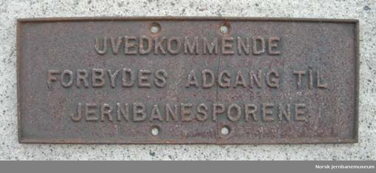 """Støpt jernskilt : """"UVEDKOMMENDE FORBYDES ADGANG TIL JERNBANESPORENE"""""""