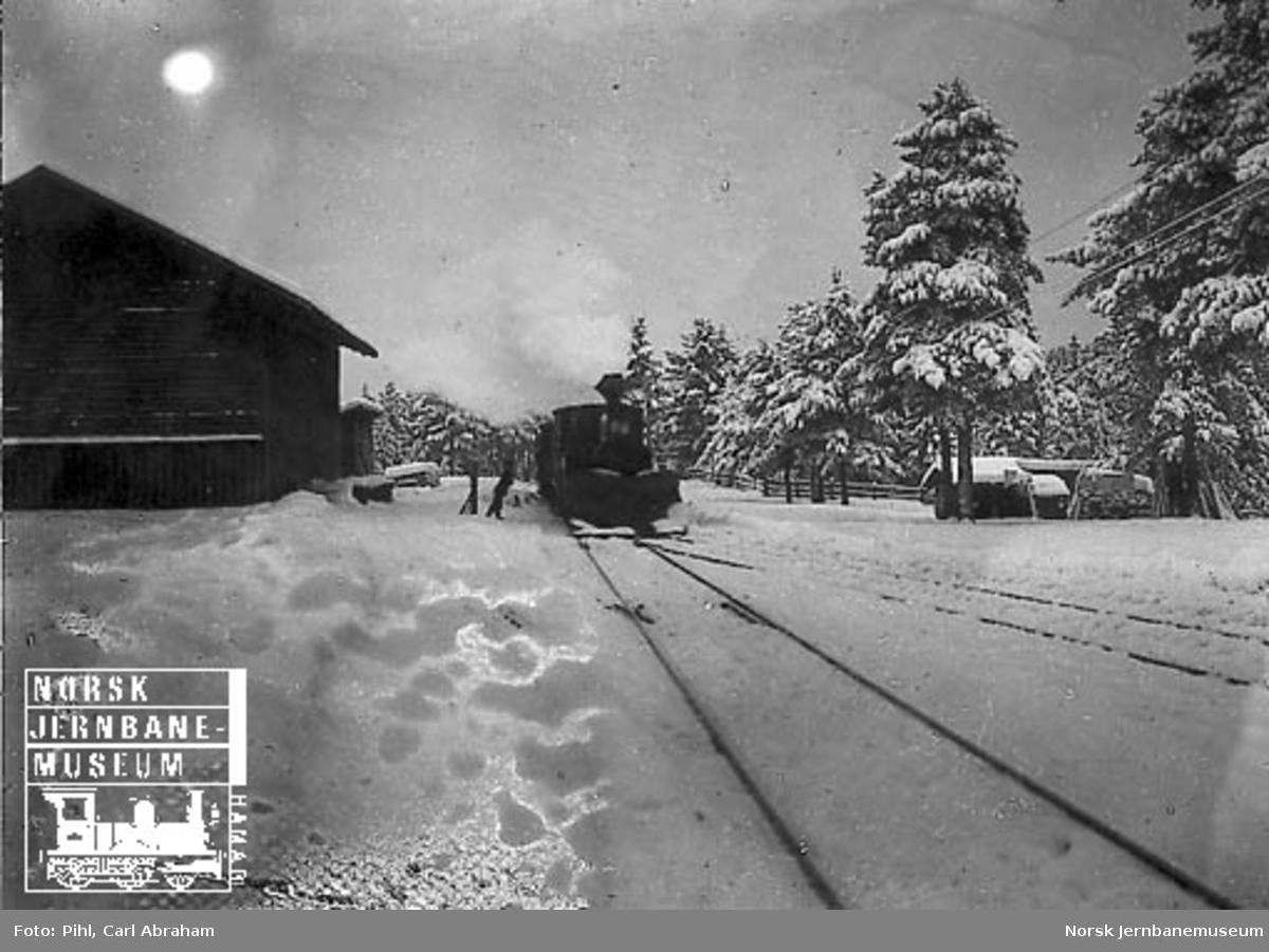 Vinterbilde med damplokomotiv type VII med stor frontplog som ankommer med tog, muligens på Rena stasjon