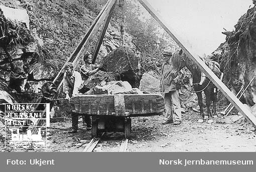 Anlegg på Sørlandsbanen vest for Kristiansand : tre mann i arbeid, stein løftes opp på en vagg med stubbebryter
