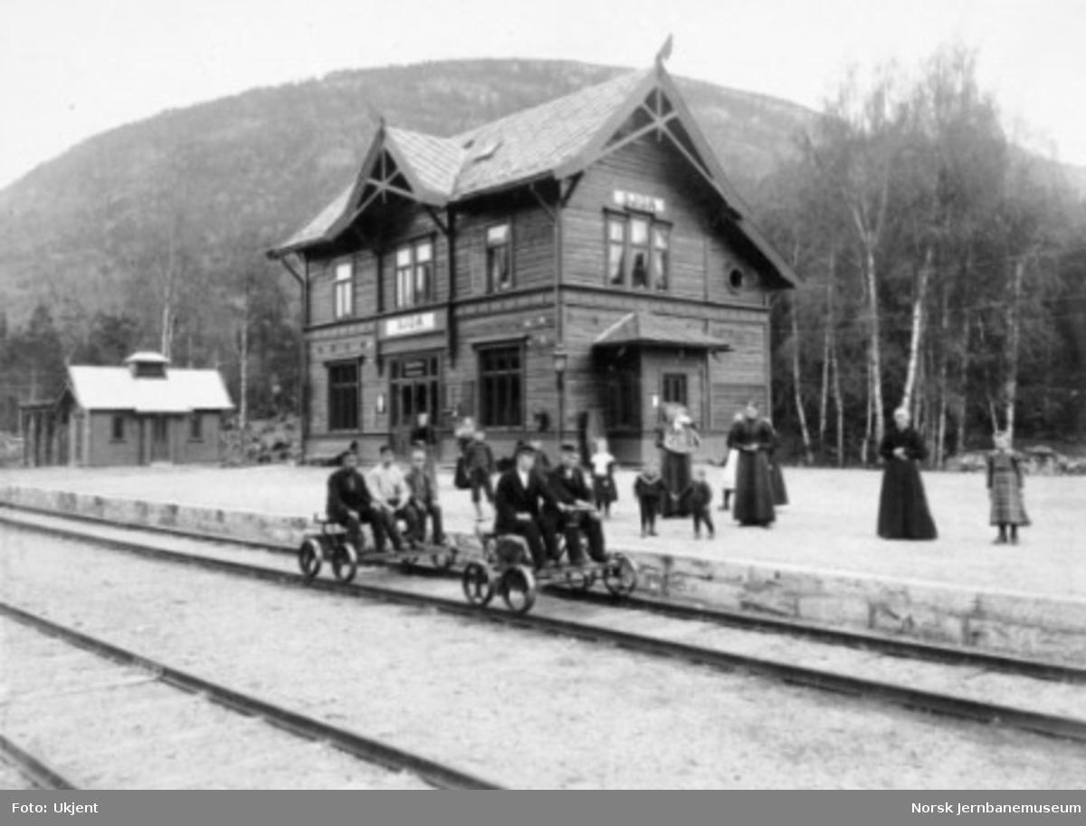 Fem menn på to dresiner i spor 1 og folk på plattformen foran Sjoa stasjonsbygning