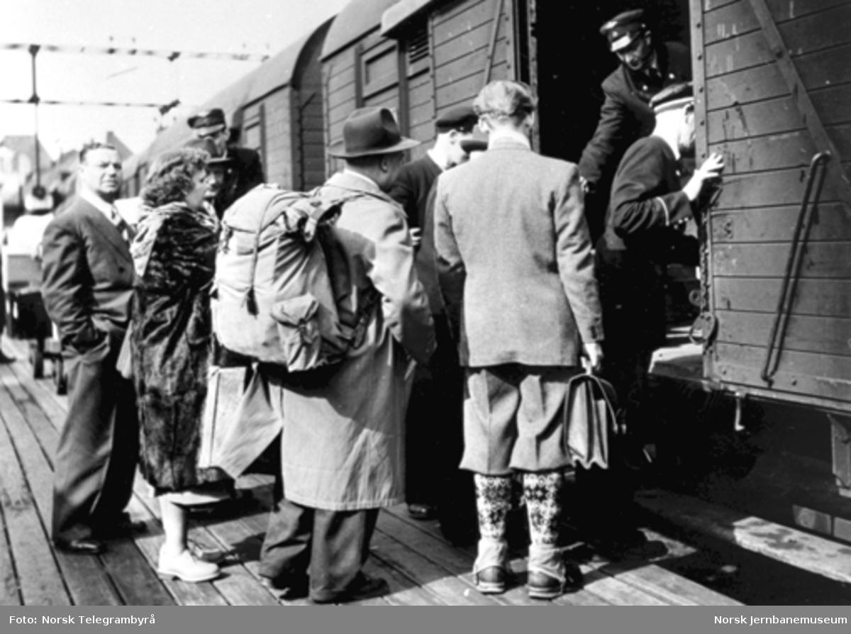 To jernbanemenn klargjør en godsvogn litra G4 for innstigning mens reisende venter utenfor