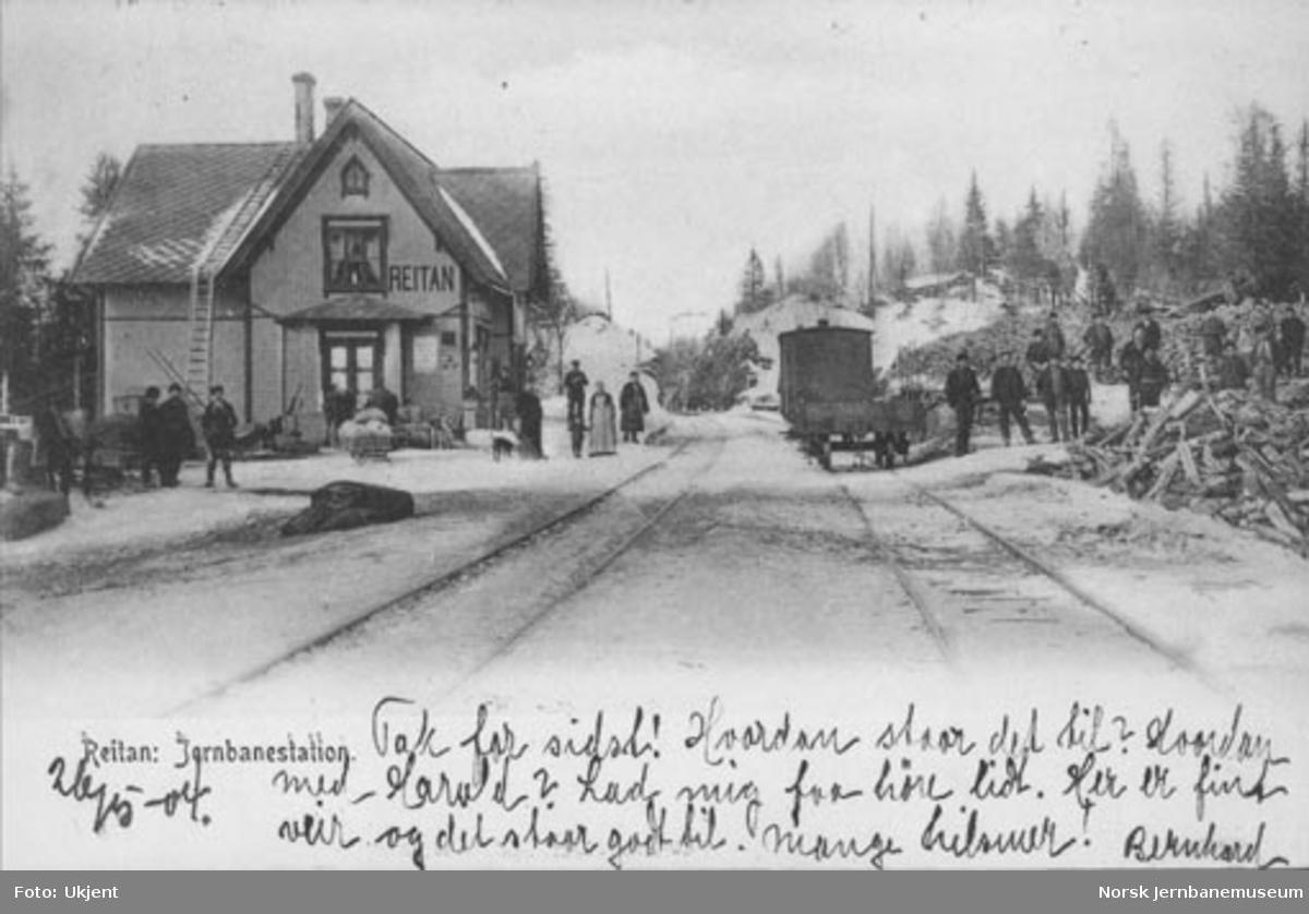Reitan stasjon med folk på plattformen og arbeidere i gang med opplasting av vogner i spor 2